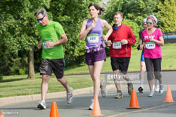 people running in road race - half_marathon stock pictures, royalty-free photos & images