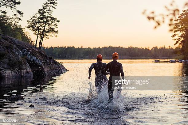 people running in water at sunset - traje de mergulho - fotografias e filmes do acervo