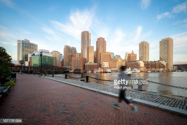 people running near boston harbor and financial district at sunrise in boston, massachusetts, usa. - boston massachusetts stock pictures, royalty-free photos & images