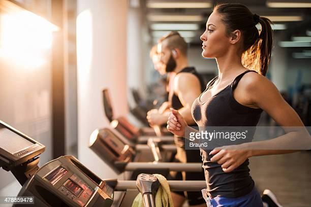 people running on a treadmill in health club. - gym stock pictures, royalty-free photos & images