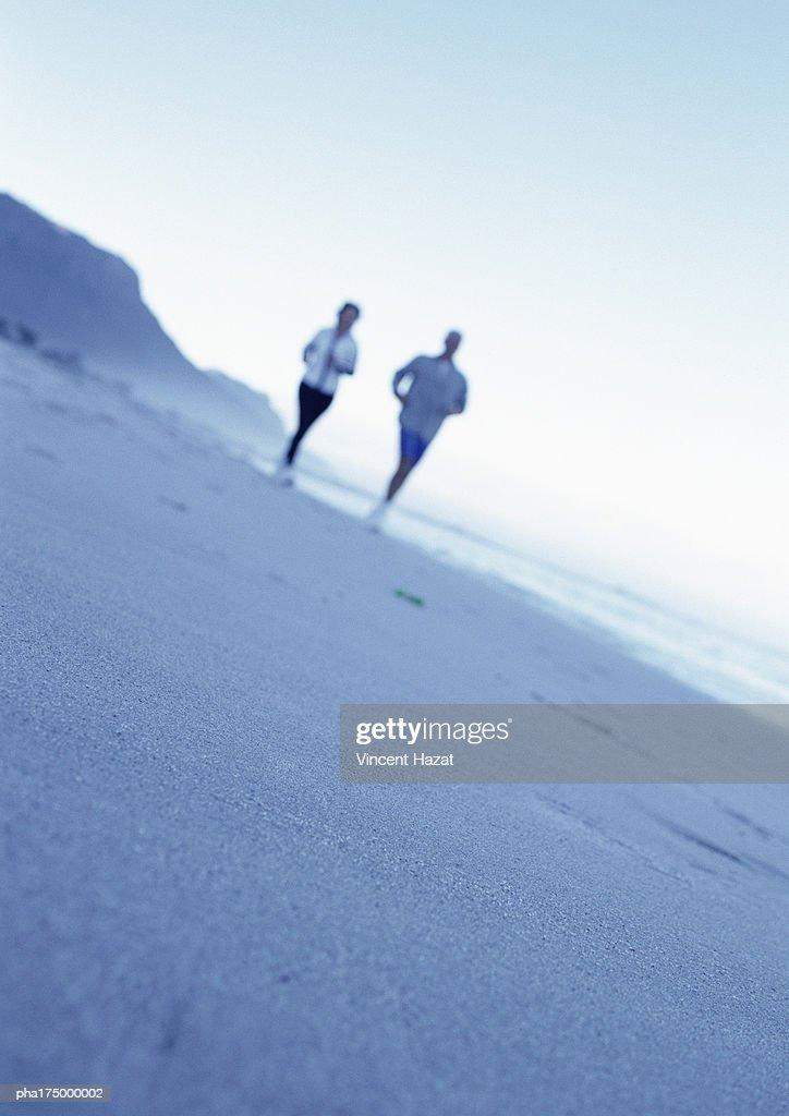 People running on beach, blurred : Stockfoto