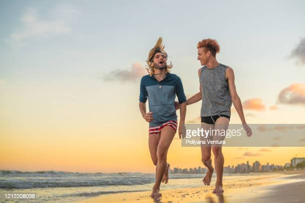 people running on the beach at sunset - gay men swimwear stock pictures, royalty-free photos & images