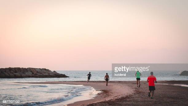 People running on the Mediterranean beach at twilight time