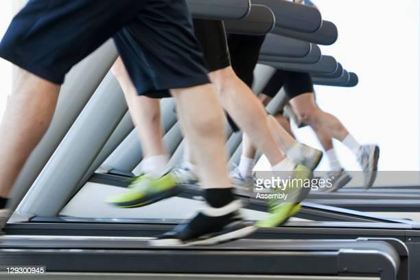 people running on treadmills in health club - unterer teil stock-fotos und bilder