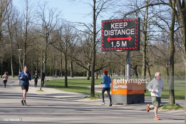 People running pass a sign urging people to practice social distancing and keep 15 meters at the Vondelpark on March 22 2020 in...