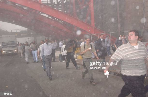 People rush away from the collapsing World Trade Center September 11 2001 after two hijacked airplanes ran into the two towers in New York City