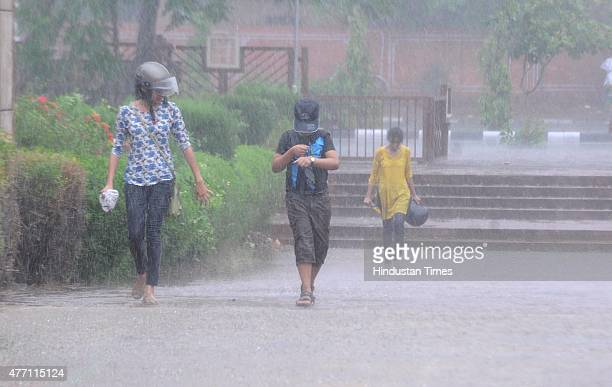 People rush for shelter during a heavy rain on June 14 2015 in Jaipur India The city sizzling as heat wavelike conditions prevailed across the city...