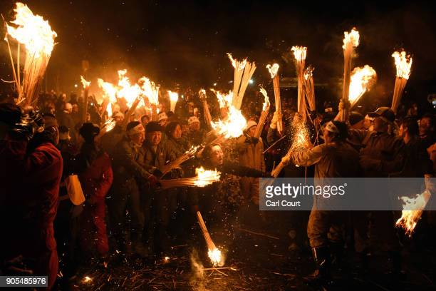 People rush forward with flaming sticks as they try to set fire to a wooden shrine that is protected by men from Nozawaonsen village during the...