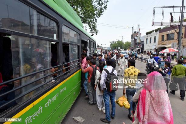 People rush onto public transport after metro service operations on the Yellow Line were hit at around 930 am due to the breakdown of overhead wires...