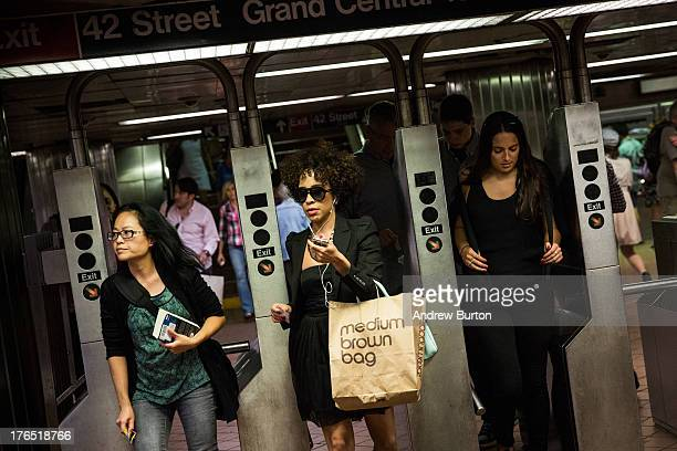 People rush through the New York City subway system at rush hour on August 14 2013 in New York City At an average of 48 minutes one way New Yorkers...
