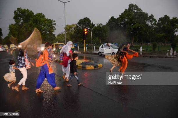People rush to find shelter as a wind storm envelopes the national capital of Delhi bringing a sudden weather change on the eve of May 13 2018 in New...