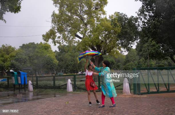 People rush to find shelter as a wind storm envelopes the national capital of Delhi bringing a sudden weather change on the eve of May 13, 2018 in...