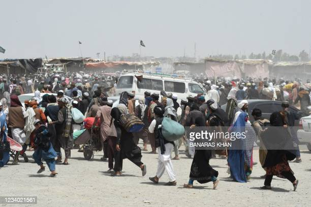 People rush towards a border crossing point in Pakistan's border town of Chaman on July 17 after Pakistan partially reopened its southern crossing...