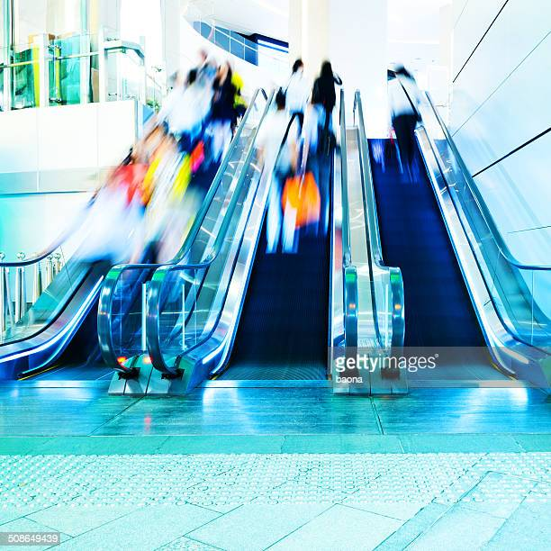 people rushing in escalators - shopping centre stock photos and pictures