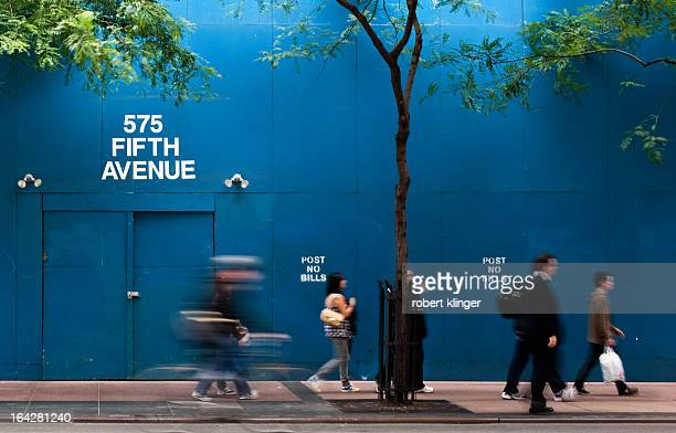 CONTENT] People rushing past a Blue Wall located in front of a construction site at 575 Fifth Avenue NYC