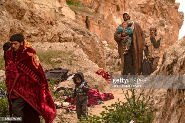 People said to be members of the Islamic State group by the USbacked Syrian Democratic Forces exit with children from the village of Baghouz in the...