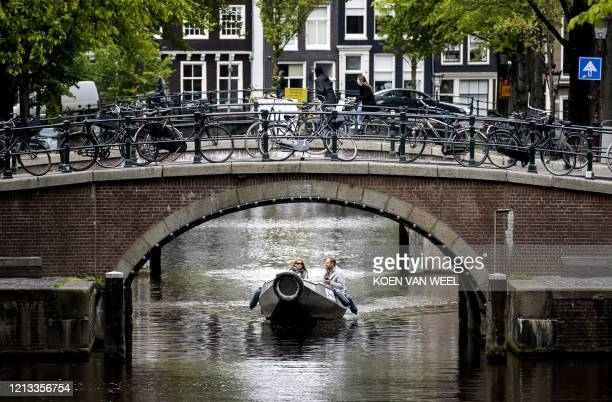 People sail on a sloop in the canals of Amsterdam, The Netherlands, on May 16, 2020 after the sailing ban, imposed every weekend, has been lifted due...