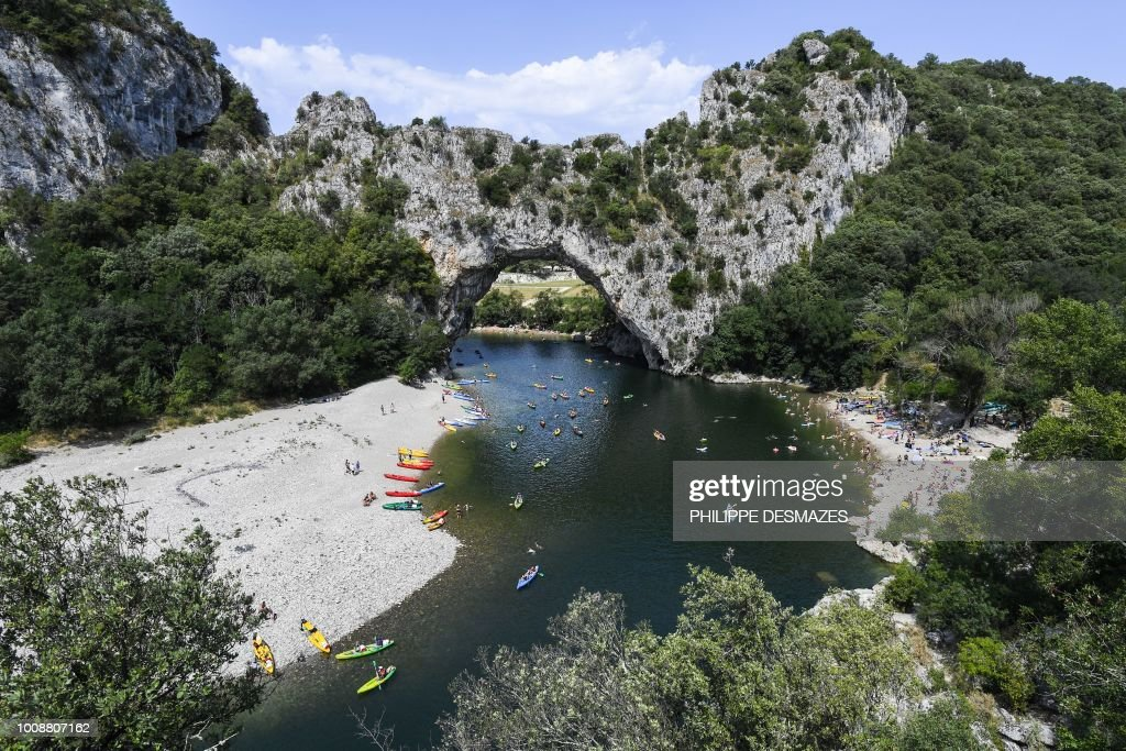 People Sail On Canoes Under Le Pont D Arc Rock On The