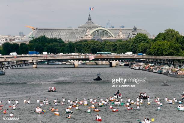 People sail on the Seine river in front of the Grand Palais museum in Paris on June 23 during an event to promote the candidacy of the city of Paris...