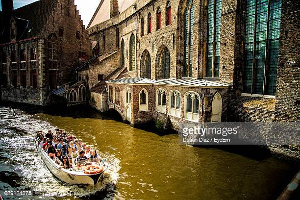 People Sailing Boat In Canal Against Buildings