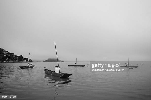 People Sailing Boat On Lake Against Sky