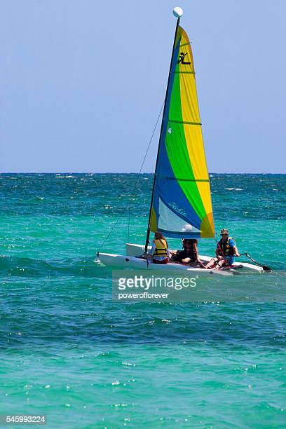 people sailing on a catamaran in the bahamas - catamaran sailing stock photos and pictures