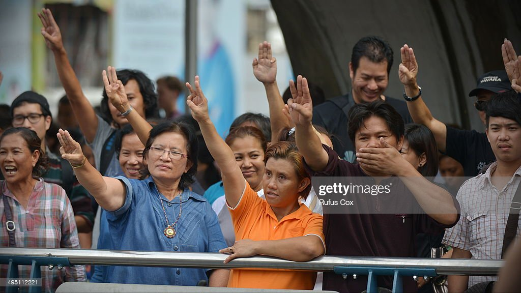 People salute in opposition to Thailand's coup on June 1, 2014 in Bangkok, Thailand. Thai soldiers temporarily closed off the city centre shopping area to prevent any further anti-coup demonstrations from protestors. The ruling Thai military has outlawed political protest and criticism of their regime, meanwhile numerous worldwide embassies have issued warnings to citizens traveling to or throughout Thailand to travel with caution.