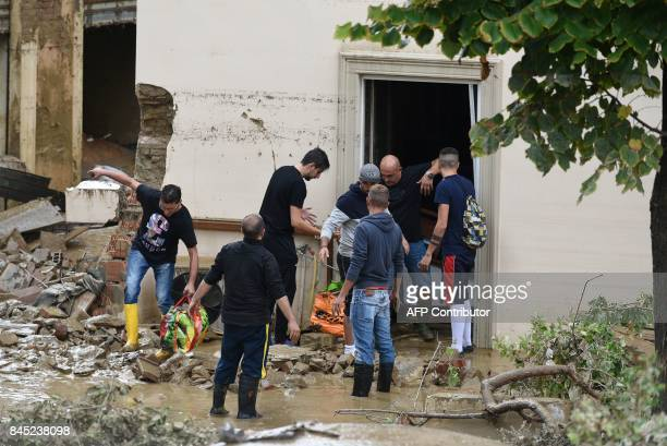 People salvage belongings as they empty a house in the Livorno area flooded after heavy rain on September 10 2017 At least six people have died in...