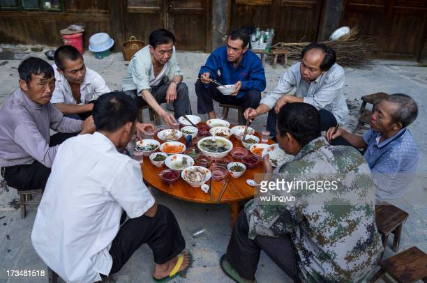 People sat around a table to have dinner together after they help their neighbour to make a house in Zhaoxing Dong village of Guizhou privince,China.