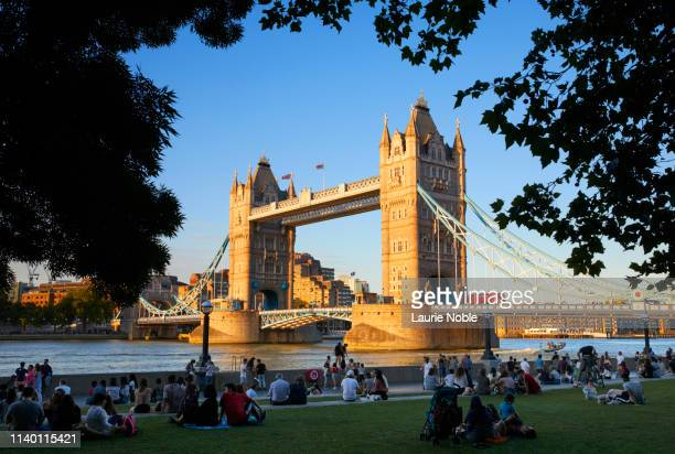people sat on grass in front of tower bridge at sunset, london, england, great britain - international landmark stock pictures, royalty-free photos & images