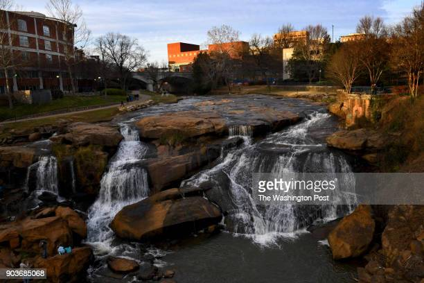 People scamper along the rocks and sidewalks in Falls Park on the Reedy in the downtown area December 27 2017 in Greenville SC