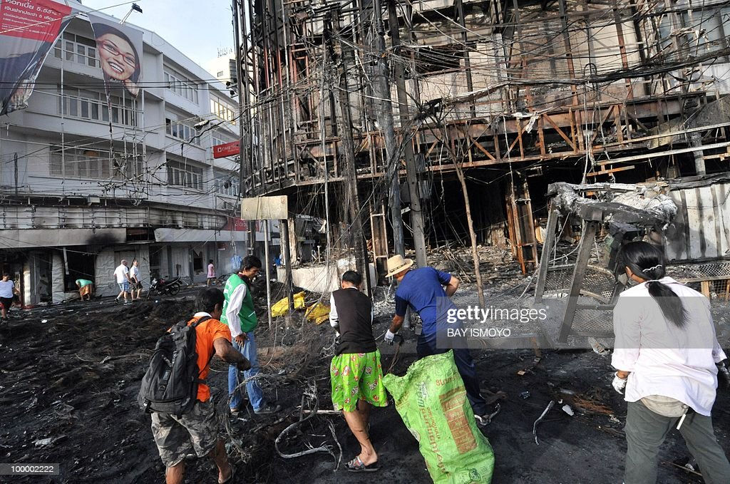 People scavenge for electric wires on Rama IV boulevard in downtown Bangkok on May 20, 2010 where traces of burnt barricades and tyres remain. Plumes of smoke hung overhead as Bangkok emerged from an curfew aimed at quelling mayhem unleashed by enraged anti-government protesters targeted in an army offensive on May 2010.