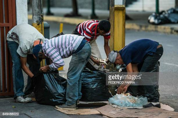 People scavenge for food in the streets of Caracas on February 22 2017 Venezuelan President Nicolas Maduro is resisting opposition efforts to hold a...