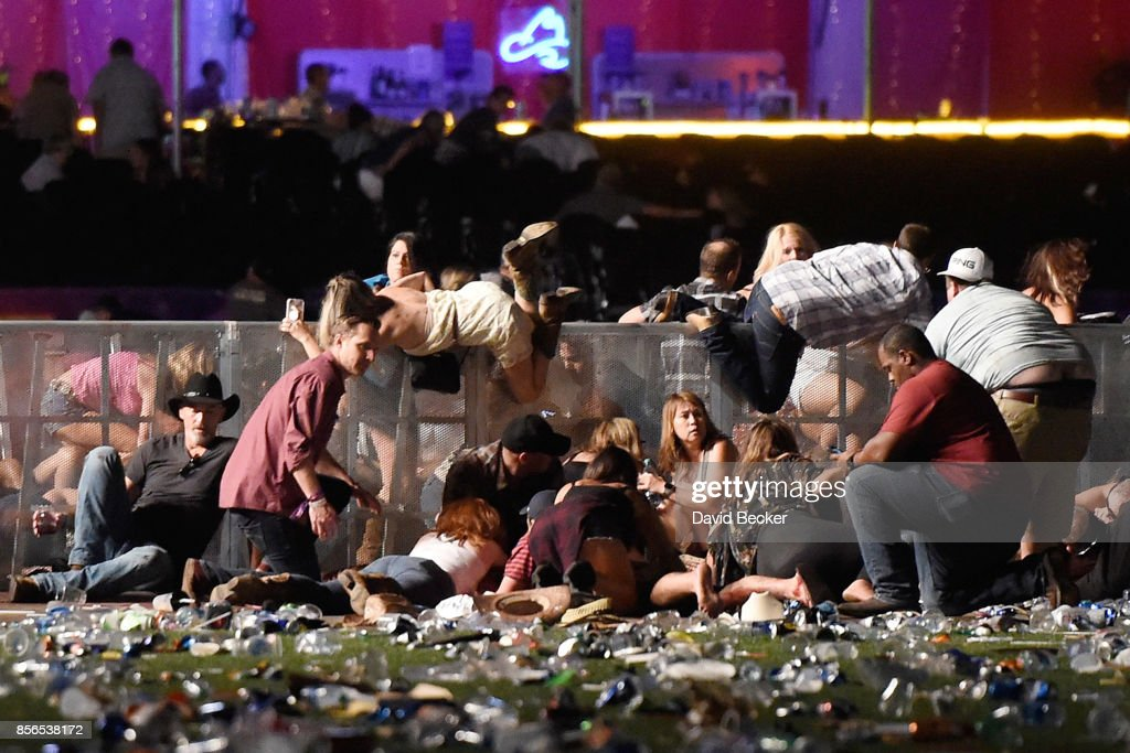 People scramble for shelter at the Route 91 Harvest country music festival after apparent gun fire was heard on October 1, 2017 in Las Vegas, Nevada. A gunman has opened fire on a music festival in Las Vegas, leaving at least 20 people dead and more than 100 injured. Police have confirmed that one suspect has been shot. The investigation is ongoing.