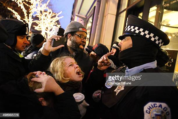People scream at cops as they protest the shooting death of Laquan McDonald during a clash with Chicago police officers outside of a Banana Republic...