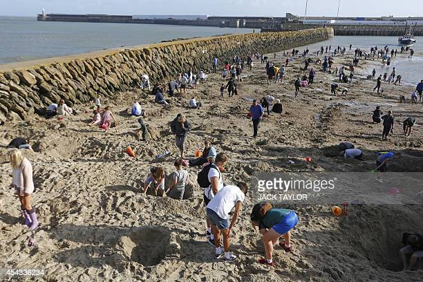 People search a beach in Folkestone southeast England on August 29 2014 for gold bullion buried there by German artist Michael Sailstorfer as part of...