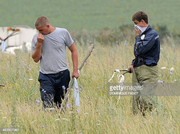 People search for bodies on July 18 2014 at the site of the crash of a Malaysian airliner carrying 298 people from Amsterdam to Kuala Lumpur near the...