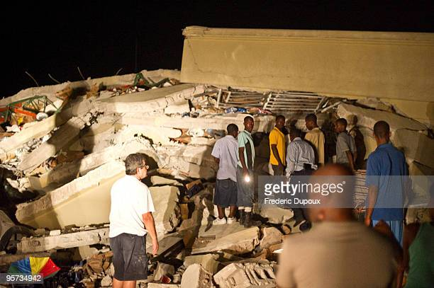 People search for survivors amongst the rubble of the Caribbean Super Market in Delmas on January 12 2010 in PortauPrince Haiti A 70 earthquake...