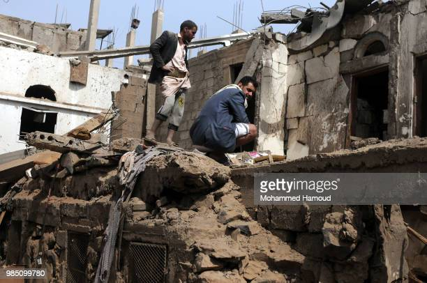 A man enters a destroyed house through a hole in a room's wall after it was destroyed by an airstrike of the Saudiled coalition on June 25 2018 in...