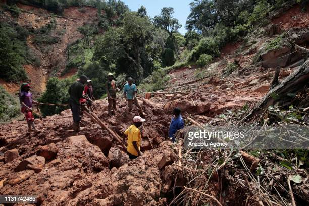 People search for the body of Agrreement Mungana who died after Cyclone Idai hit the area in Chimanimani 450 km east of the capital Harare Zimbabwe...