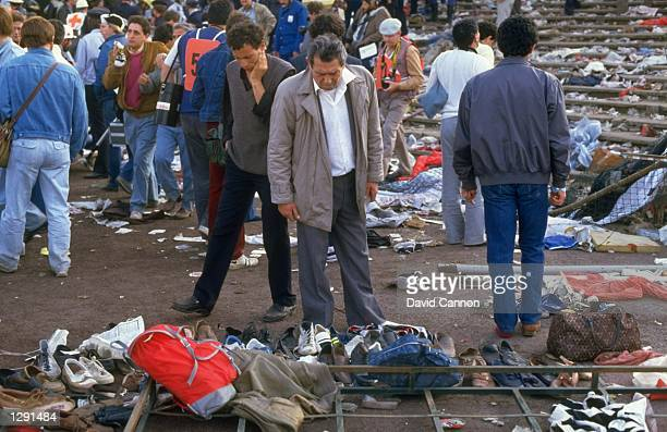 People search for their belongings after the crowd riots during the European Cup match between Liverpool and Juventus at the Heysel Stadium in...
