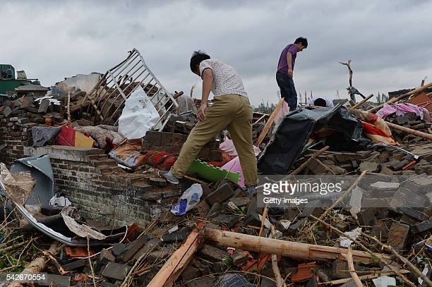 People search for their belongings on the rubble of collapsed houses on June 24 Jiangsu Province of China Heavy hail and a strong tornado has hit...