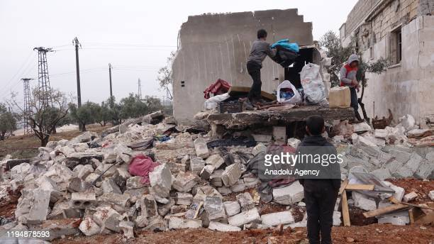 People search their belongings among wreckage of a house is seen after Russian forces carried out air strikes over at Kafr Taal village in Idlib a...