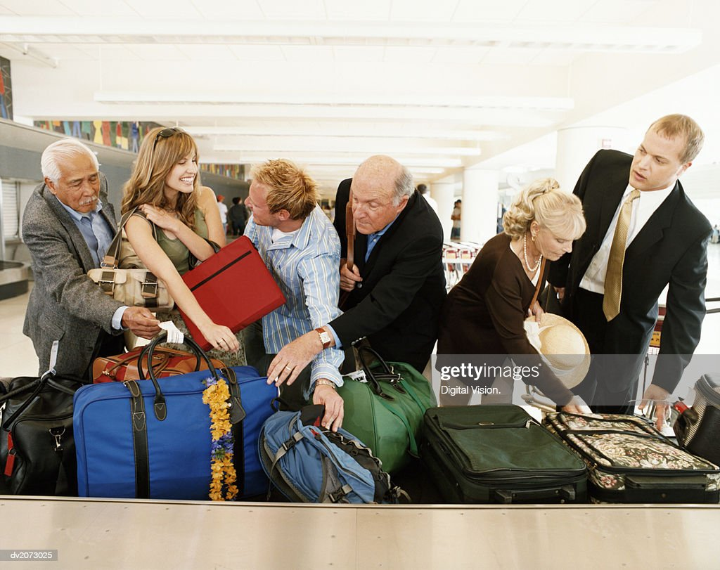 People Searching For Their Luggage at an Airport Baggage Collection : Stock Photo