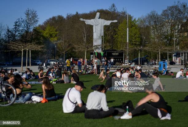 People seat in a park on April 19 2018 in Fribourg western Switzerland next to a replica of Rio de Janeiro's statue of Christ the Redeemer The 125...