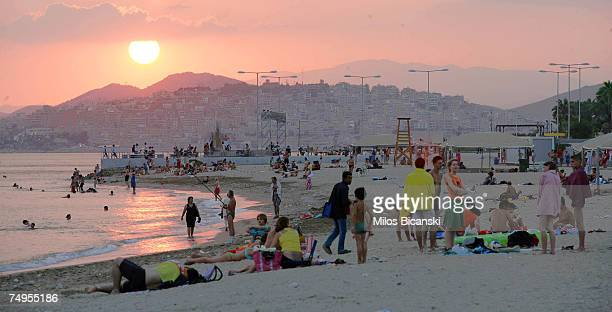 People seek refuge from the heat in the sea by a beach at sunset on June 29 2007 in in Athens Greece Organised beaches remain open until midnight...