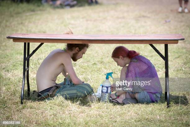 People seek shade as temperatures reach record levels at the Glastonbury Festival at Worthy Farm in Pilton on June 21 2017 near Glastonbury England...