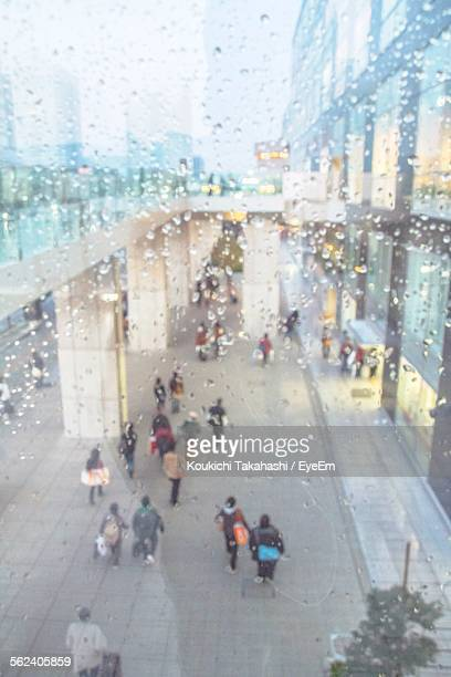 People Seen At Shopping Mall Through Wet Glass Window