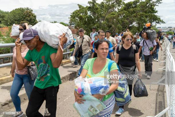 People seen carrying goods over the SImon Bolivar bridge at the Venezuela Colombia border crossing in Cucuta. Thousands of Venezuelans cross the...