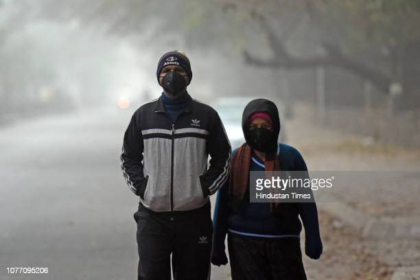 People seen covered in warm clothes and antipollution masks to protect themselves from cold weather and pollution at Safdarjung Enclave Market on...